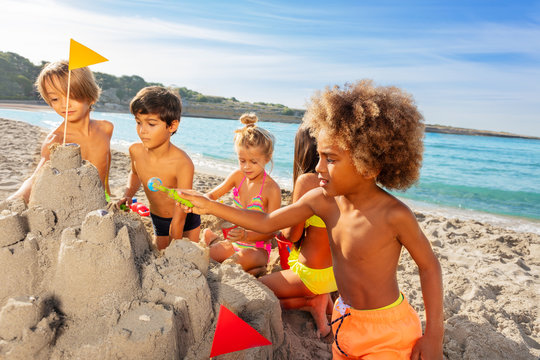 Kids creating sandcastle on the beach in summer