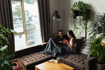 Couple having soup on sofa in living room