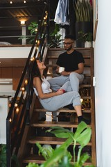 Couple interacting with each other while having coffee in stairs