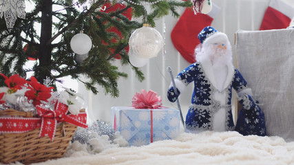 Stylish white christmas interior with decorated fir trees with Santa Claus gift box socks and basket