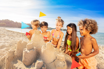 Happy kids creating sandcastle using sandpit toys