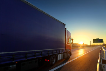 Truck transport on the road at sunset Wall mural
