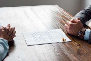 cropped shot of hands of lawyer and client, divorce decree and wedding rings on table