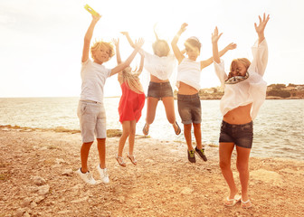 Cute teens jumping together on the beach in summer