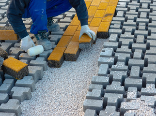 Paving stone worker is putting down pavers during a construction of a city street onto sheet nonwoven bedding sand and fitting them into place.