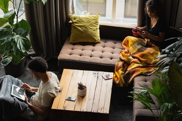 Couple using mobile phone and digital tablet while having coffee
