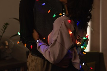 Romantic couple wrapped in fairy lights embracing each other