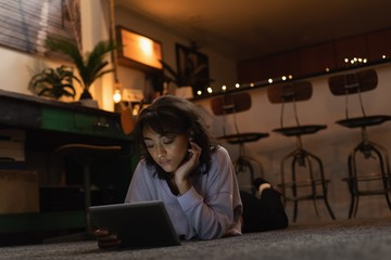 Woman using digital tablet on floor at home