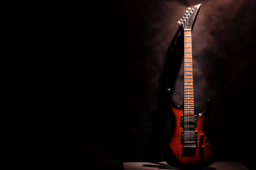 Red electric guitar on a dark background.