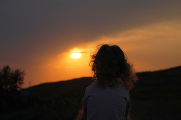 silhouette of girl on top of mountain at sunset