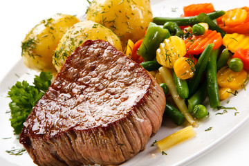 Grilled beefsteak with boiled potatoes and vegetable salad on white background