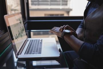 Businessman using smartwatch in office