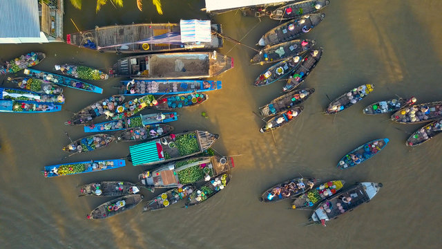 AERIAL: Cinematic shot of people in the floating market on a scenic evening.
