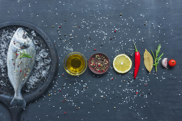 elevated view of arranged ingredients near tray with uncooked fish on black table