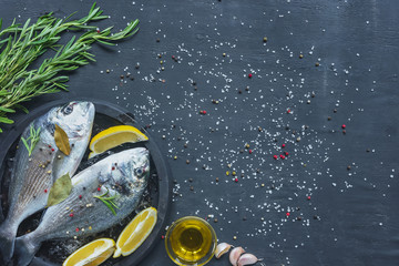 view from above of raw fish with lemon, bay leaves and rosemary in tray on black table covered by salt and pepper