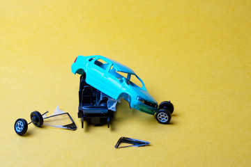 toy car broken into pieces, wheels and glass fell off
