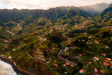 Aerial view of the Porto da Cruz town in the north shore of Madeira island with mountain range in the heavy clouds. Madeira, Portugal.