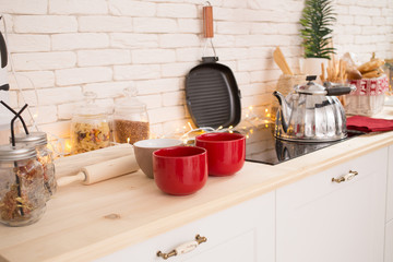 Interior light kitchen with red decor and Christmas decorations. Preparing holiday dinner at home on the kitchen concept. Decorated new Year fir. Selective focus