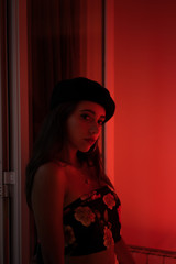 Charming young lady in tank top and beret in redness