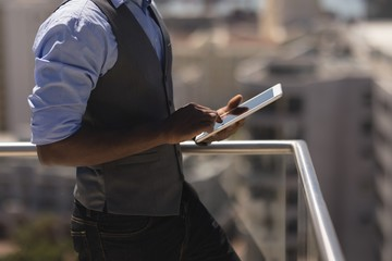 Businessman using digital tablet at terrace in office