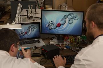 Robotics engineers working at desk in warehouse