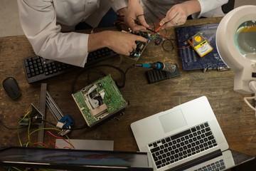 Robotics engineers assembling circuit board at desk