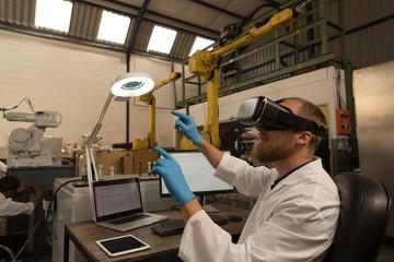 Robotics engineer using virtual reality headset at desk