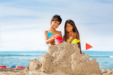 Kids having fun building sandcastle on the beach