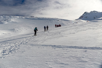 Some snowshoe hikers walk through the snow-covered Alps in winter in the canton of Graubünden in Switzerland.