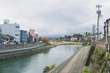 Urban or park background featuring Saigawa river and bridges across in residential district of Kanazawa, Japan, in cloudy autumn day in November.