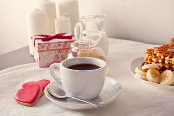 Coffee and a heart shaped cookies, honey, milk and waffles
