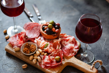 Meat plate, cold smoked pork, jamon, prosciutto, salami served with wine, nuts and olives