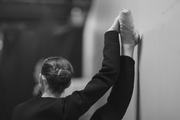 Ballerina in pointe near a wall makes stretching, lifting leg up