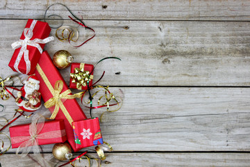 Red Christmas presents and holiday ornaments on rustic wood background