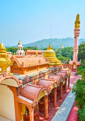 Enjoy the beauty of Sitagu International Buddhist Academy pagoda from above with a view on lush greenery of Sagaing Hill on the background, Myanmar.
