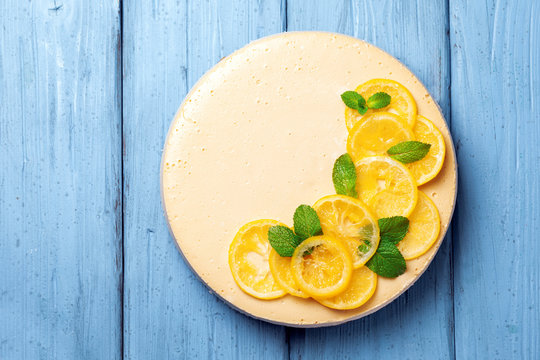 Top view of lemon cheesecake decorated with citron and mint on wooden background. Healthy organic summer dessert pie