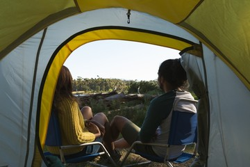 Couple relaxing near tent in the forest