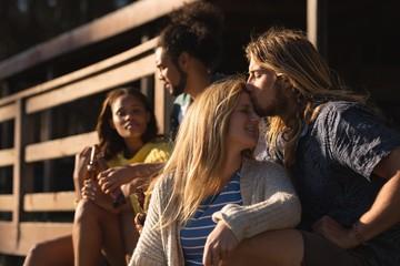 Man kissing woman head on cabin