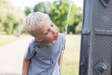 Little boy drink water in the park