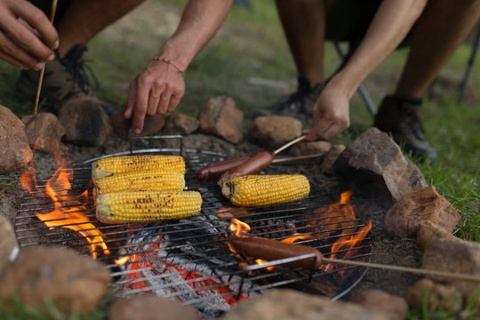 Men roasting sausages and corns on barbeque