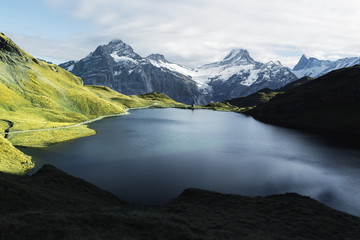 Picturesque view on Bachalpsee lake in Swiss Alps mountains. Snowy peaks of Wetterhorn, Mittelhorn and Rosenhorn on background. Grindelwald valley, Switzerland. Landscape photography