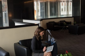 Businesswoman using digital tablet in lobby