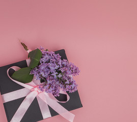 Gift box with pink ribbon on the pink background, decorated with lilac. Mother's Day. Birthday Valentine's Day. Copy space
