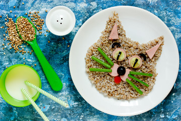 Food art idea for kids - buckwheat cat, animal face buckwheat porridge with sausage and vegetables for healthy lunch