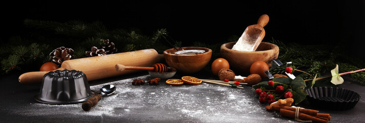 Baking ingredients for homemade pastry on wooden background with cookies and spieces