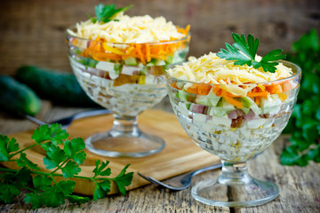 Festive layered salad serving in glass from smoked chicken fillet, egg, cucumber, carrot, potato and cheese