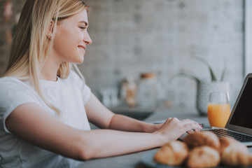 Always online. Cute woman wearing white T-shirt and sitting at table in kitchen while connecting with her laptop