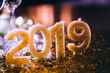 New Years Eve celebration background with pair of flute,candles forming the 2019 number, glitter and defocused background, with christmas tree light forming a nice bokeh, holiday concept, frontal view