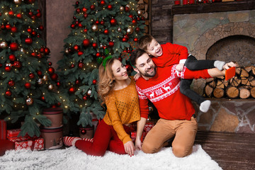 Young family: father, mother and son in warm red sweaters doing selfie by red smartphone with decorated christmas tree near fireplace during winter holidays. Merry Christmas and Happy New Year concept