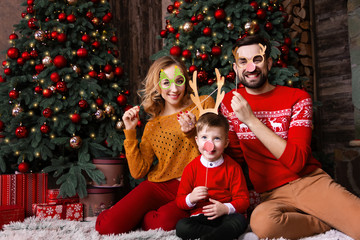Happy family husband male man, wife female woman present gift for son boy during winter holiday: Christmas and 2019 New Year at home with decorated christmas tree. Merry Christmas and Happy New Year.